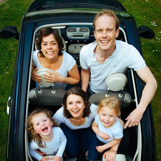 Parents with their children in a car after they have realized how to make long-distance relocation fun for kids.