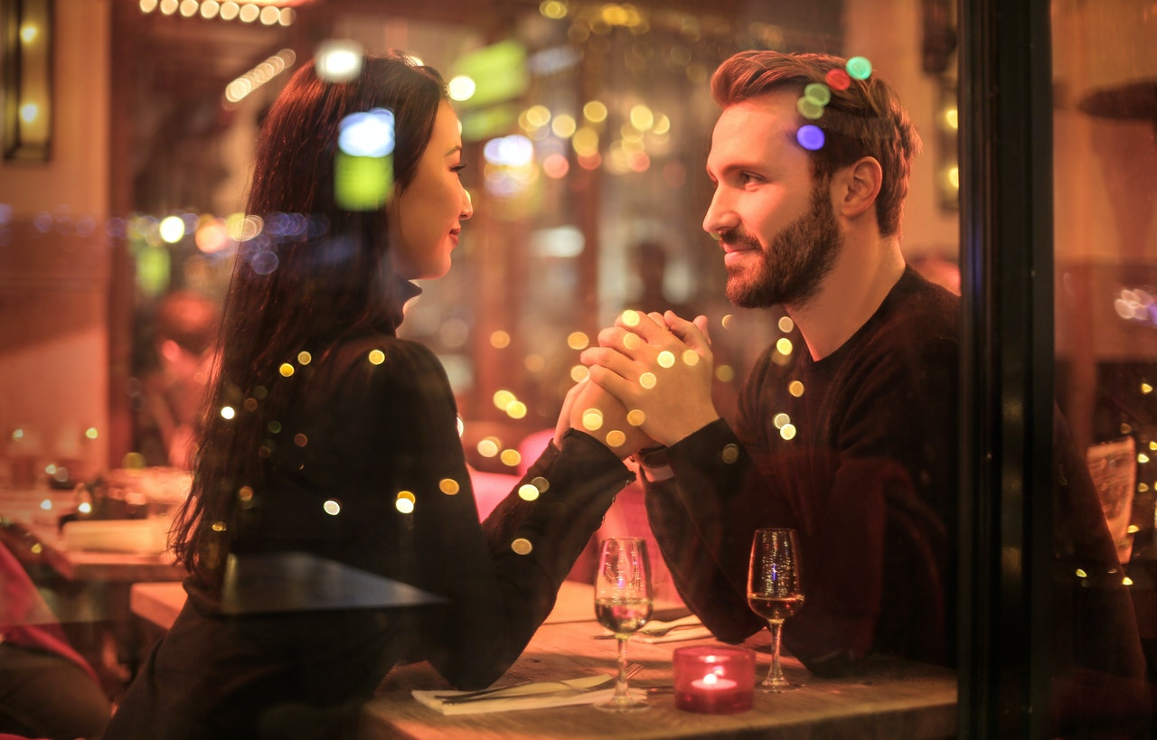 Couple holding hands and looking at each other at the restaurant