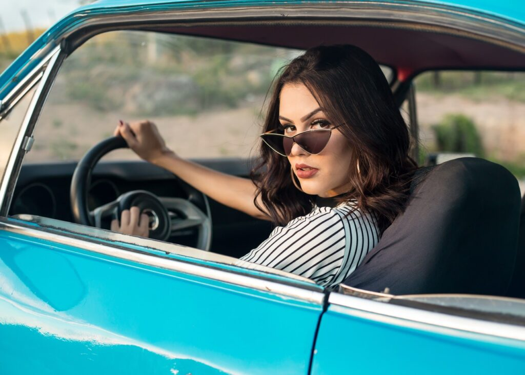 Woman with sunglasses sitting in a blue car