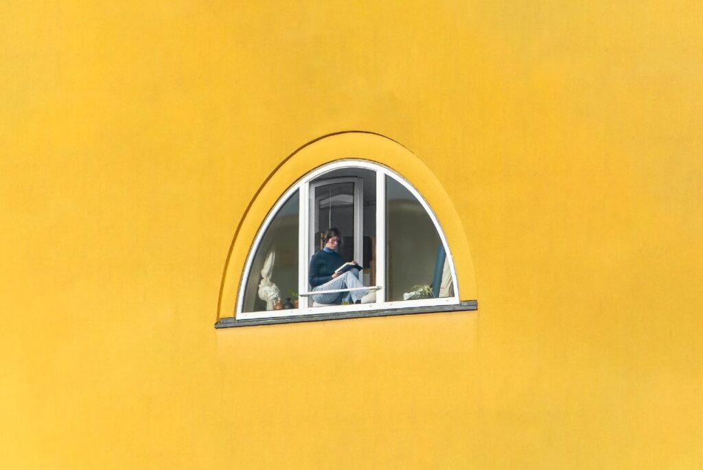 Woman sitting at the window of an ocher building while reading